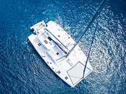 A white catamaran on a still blue sea