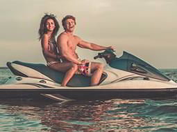 A woman and a man laughing and posing on a jet ski