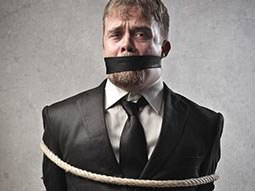 A man wearing wearing a suit tied up with rope and with a gag around his mouth