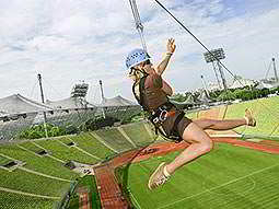 A woman on a zipline stretching over an open-air stadium