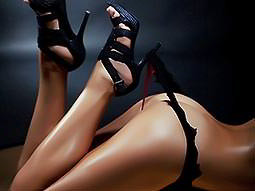 The bottom half of a woman holding her thong up with the heel of her stiletto