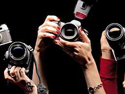 Three cameras are held in the air