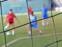 An out of focus game of football viewed through goal netting