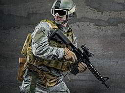 A solider wearing full combat equipment, helmet and goggles holding a rifle and looking away