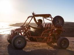 A side view of a man driving an off-road buggy, with a coastal scene in the background