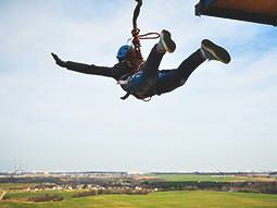 A person jumping forward off a platform, wearing a bungee jumping harness and cord