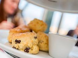 Scones with clotted cream, with people in the background
