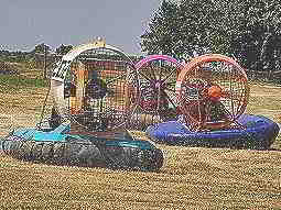 Three multicoloured hovercrafts driving through a field