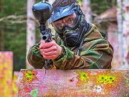 A man wearing a paintball mask standing behind a wooden board and aiming a paintball gun