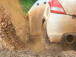 A view down the side of a white car as it splashes through a muddy puddle