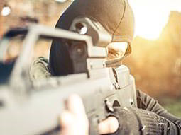 A close up of a man wearing a black balaclava aiming a rifle