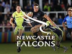 A Newcastle Falcons player running with the ball and being tackled during a game of rugby