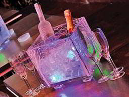 A clear ice bucket containing a bottles of vodka and champagne on a table surrounded by champagne flutes