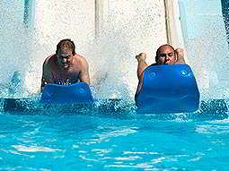 Two men landing in a swimming pool on blue floats, at the end of a slide