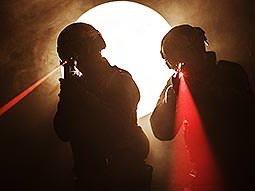 Two men aim guns emitting visible red laser beams past the camera