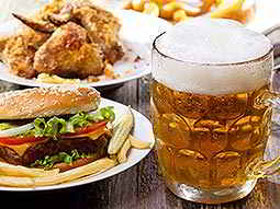 A pint of beer next to a burger and chips meal, with more food in the background