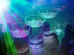 Close up of a line of filled shot glasses overlaid with green laser lights