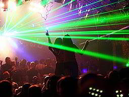 A large group of people dancing in a nightclub under green laser lights