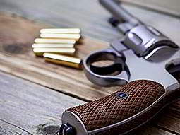 A revolver handgun lying on a wooden surface next to 6 rounds of ammunition