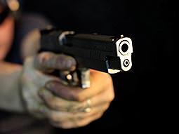 A handgun being aimed past the camera