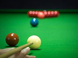 A snooker shot being lined up, with red and coloured balls in the background
