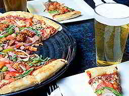A pizza on a plate, with pizza slices on napkins and a glass of beer