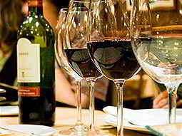 Wine glasses, both empty and filled with red wine, and a half empty bottle of red wine