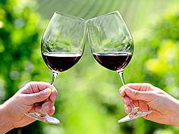 Two wine glasses, partly filled with red wine, are clinked together