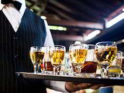 A tray of drinks being held by a man in a waistcoat