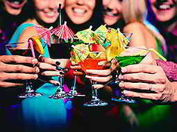 A number of multicoloured cocktails are clinked together by a group of women, out of focus in the background