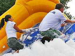 People negotiating a large inflatable obstacle covered in soap suds