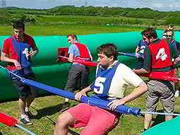 A group of people playing human table football inside a large inflatable pitch