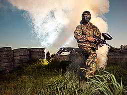A man wearing camouflage overalls and a mask standing near tyres and a plume of white smoke