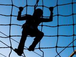 The silhouette of a man climbing on a net