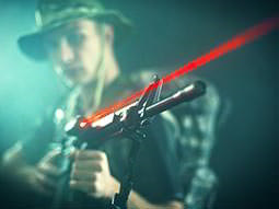 A man aiming with a red laser gun and wearing camouflage