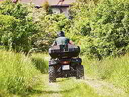 A man driving a quad bike in a field