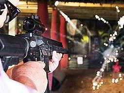 A man aiming with an air rifle at an indoor shooting range