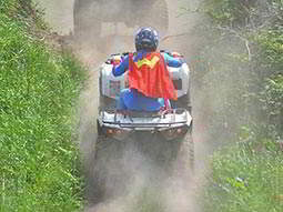 A man in a superhero costume driving a quad bike through a field