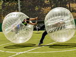Two people bouncing off each other in inflated zorbs