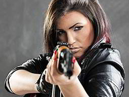 A woman in a leather jacket, aiming a gun to the camera