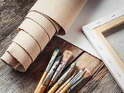 A roll of brown paper alongside a frame and paintbrushes on a wooden table