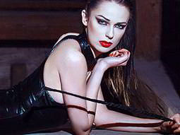 Close up of a woman wearing a leather bodysuit and holding a whip whilst lying on her front
