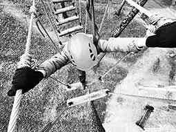 A top-down, black and white image of a person traversing a high ropes course