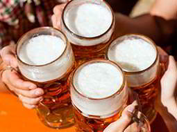 Four large glasses of beer being clinked together in the air