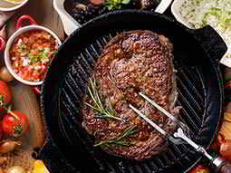 A large steak in a cast iron skillet, being stabbed with a carving fork