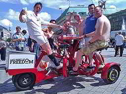 Men sitting on a red conference-style beer bike