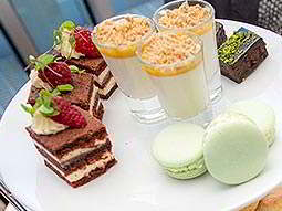 Some sweet treats including small slices of cake, macaroons and chocolate brownie bites on a white plate