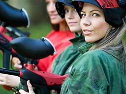 A row of women wearing overalls and holding paintball guns