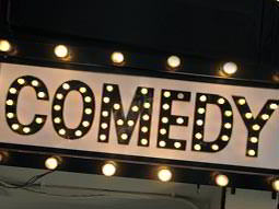 An illuminated sign reading COMEDY