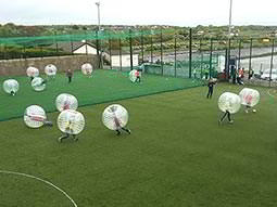 People playing bubble football on an outdoor pitch